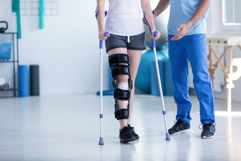 patient walking on crutches with knee brace