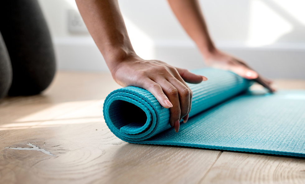 hands rolling yoga mat