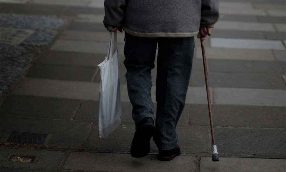elderly pain with arthritis walking with cane