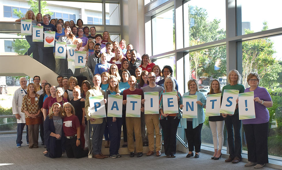 "CCMH Employees gathered for Hospital week with ""We Love Our Patients!"" signs"