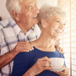 Older man and woman looking out window and smiling
