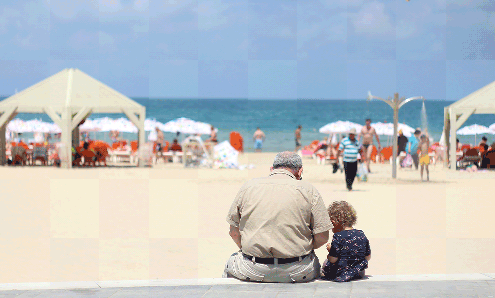 man sitting on beach with child