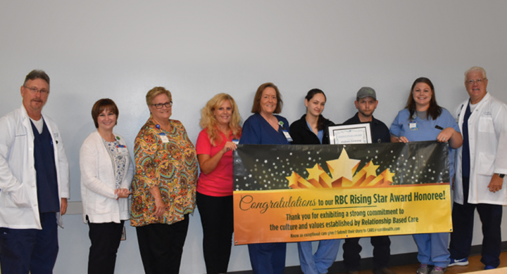CCMH Faculty holding Rising Star Award banner with Andrew Fanning