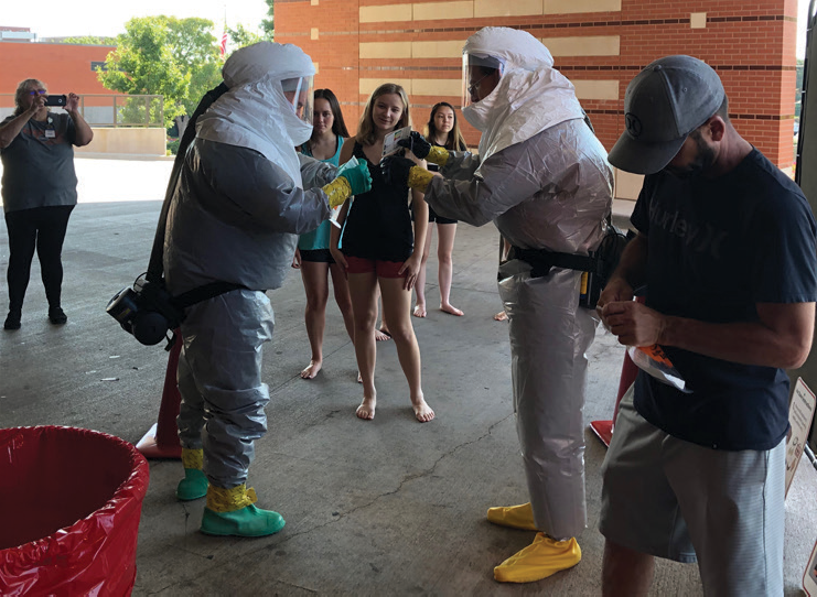 High school girls watching men in hazmat suits demonstration