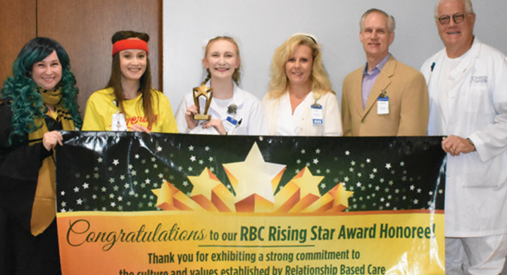 Caitlyn Reser holding award behind Rising Star banner with CCMH Staff