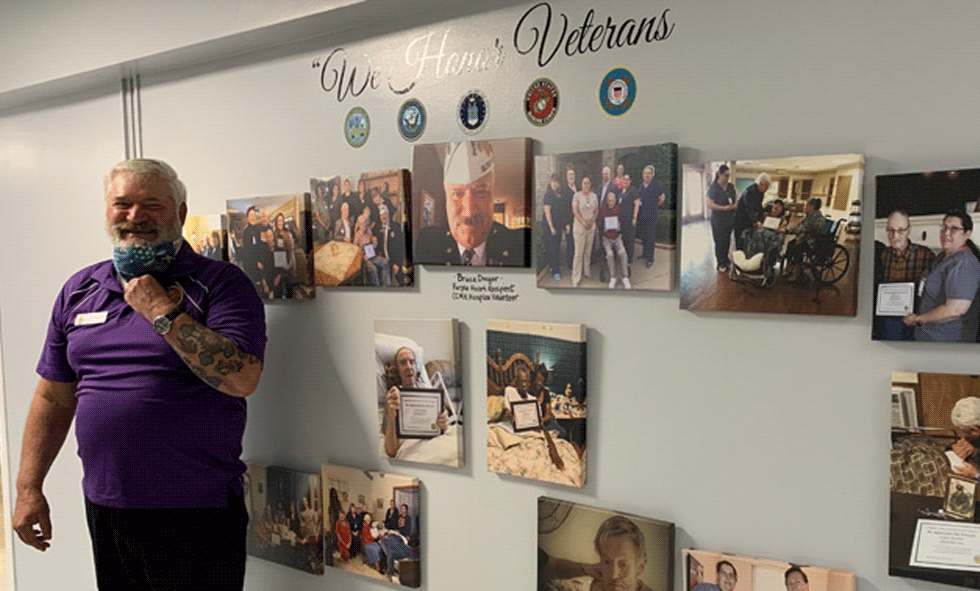 CCMH Hospice Volunteer in front of new We Honor Veterans wall