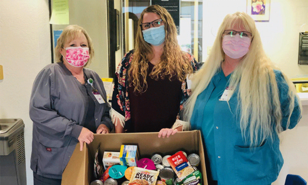 LCHC employees showing box of foods donated at their food drive