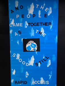 "blue poster with painted clouds and hands holding the earth reading ""And the people came together as the world stood still"""