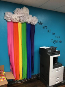 "blue wall with paper streamer rainbow with ""we are all in this together"" painted on the wall"