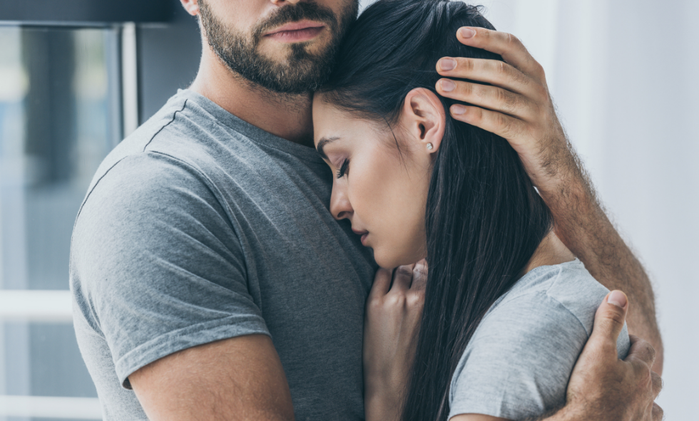 dark haired suicidal woman receiving hug from while male with beard