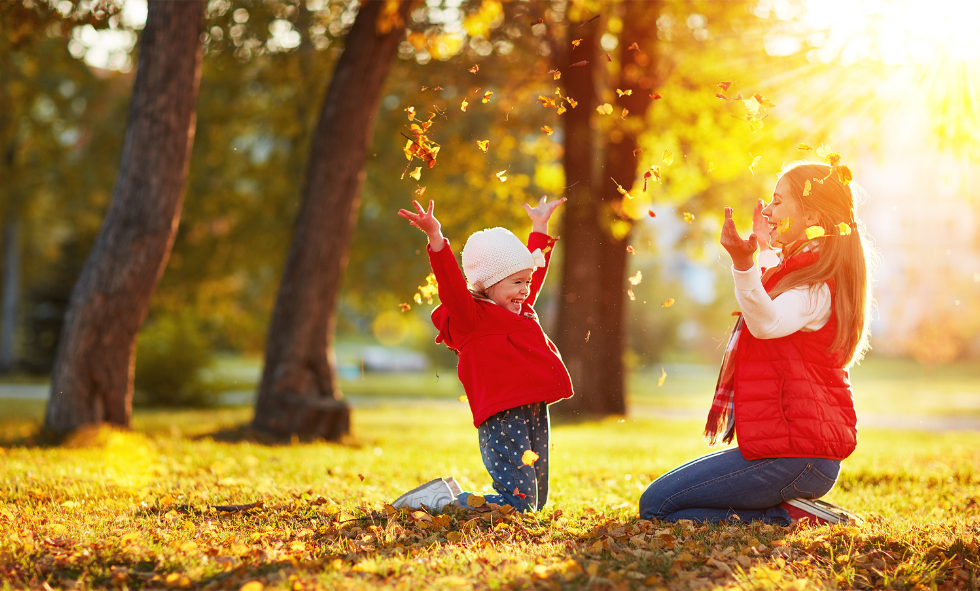 Mom and child in red jackets playing in fall gold and orange leaves