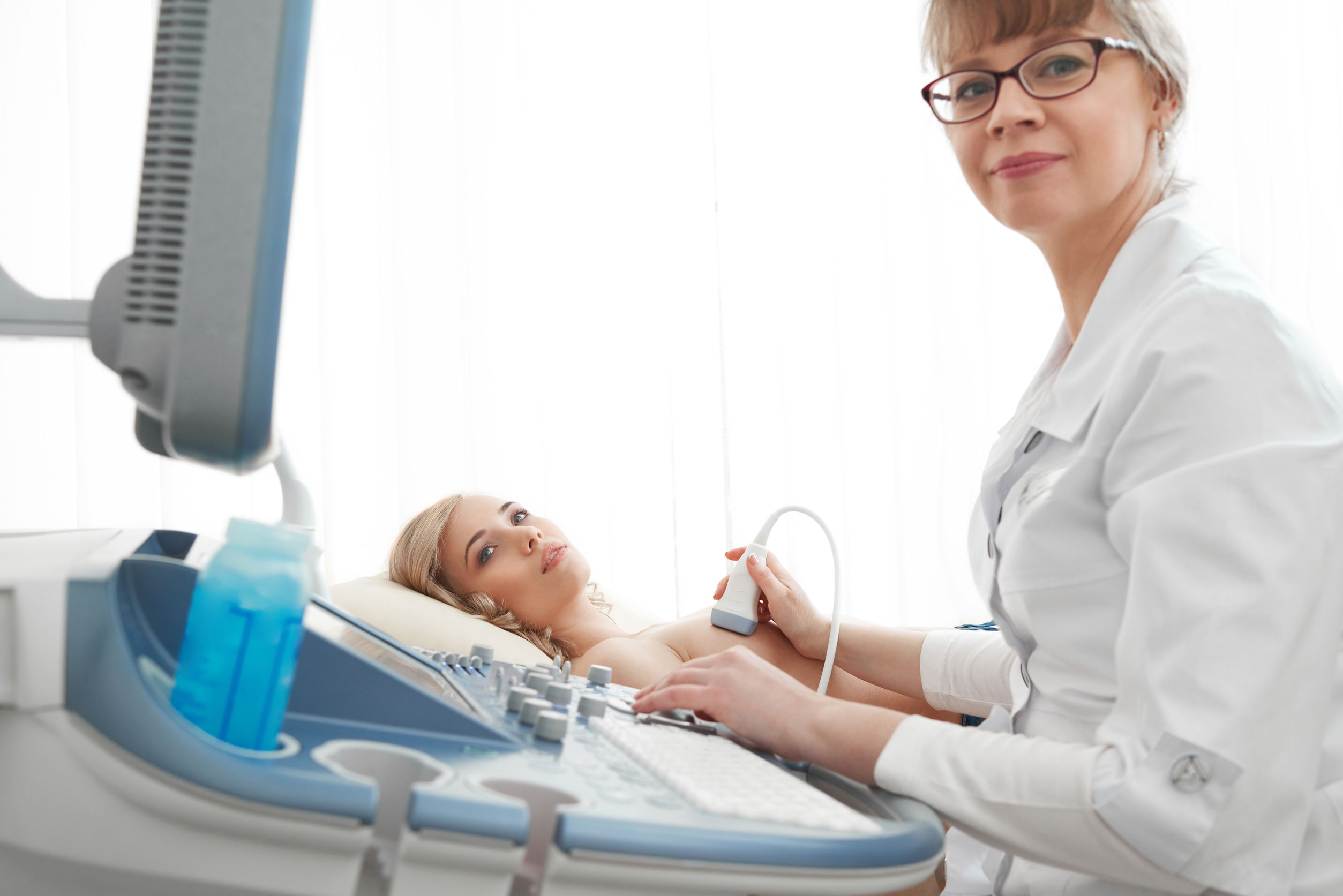 Young woman getting breast ultrasound scanning
