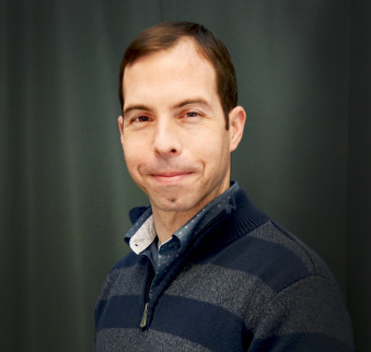 man with brown hair and grey and navy striped sweater