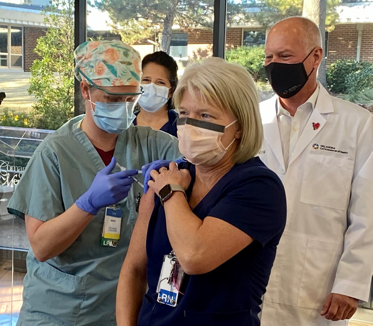 white female nurse with blonde hair receiving first COVID vaccine from CCMH employee