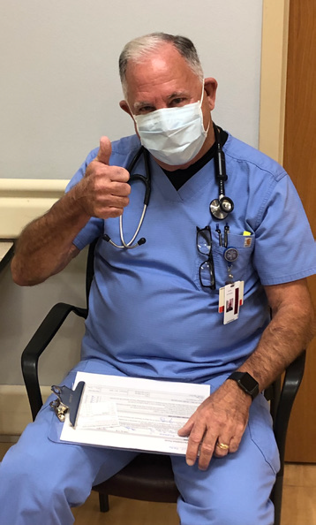 COVID vaccinated CCMH employee posing for picture with a thumbs up