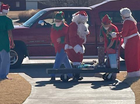 MTNRC employees dressed as Santa, Mrs. Claus, and Christmas elves arranging presents on a sleigh