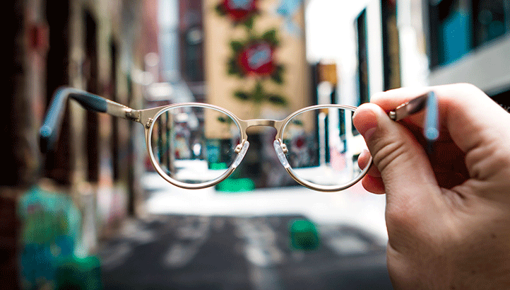 Person holding up glasses outside