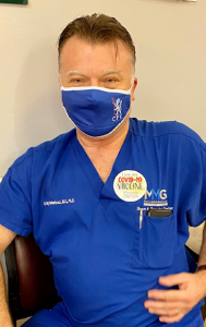 """CCMH employee posing, showing off his """"I got my COVID-19 vaccine"""" sticker"""