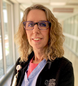 white middle-aged woman wearing CCMH scrubs with glasses and curly medium-blonde hair